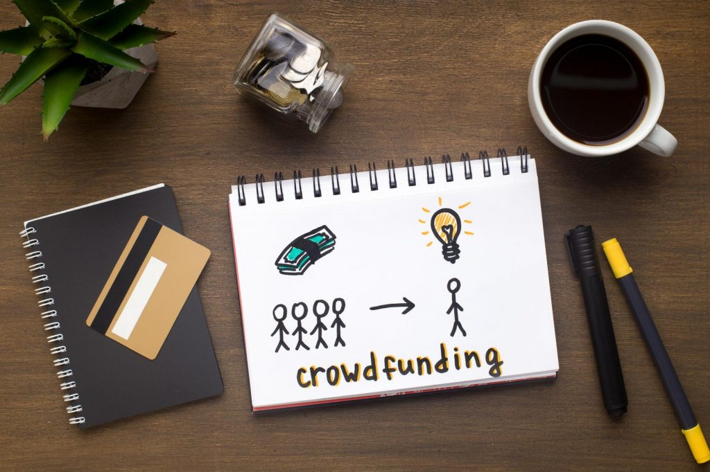 Drawing with crowdfunding concept in the notepad